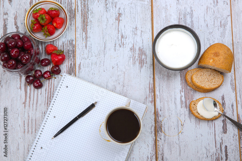 Cherry, strawberry, sour cream, bread, coffee cup, pen and notebook on ...