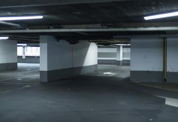 Empty parking garage illuminated by fluorescent lights.