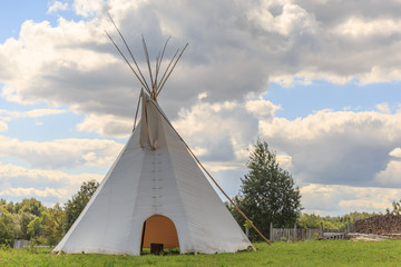 Wigwam on the field over the blue sky