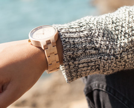 young woman wearing a wooden wristwatch in the beach