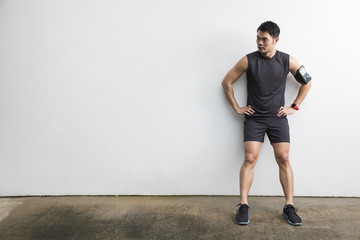 Athletic Chinese man resting after fitness exercise.