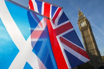 Scottish and Union Jack British flags flying in front of Westminster Palace and Big Ben under bright blue sky, London