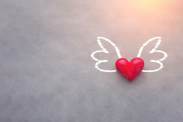 love concept with red heart object with wings drawing on grey ba