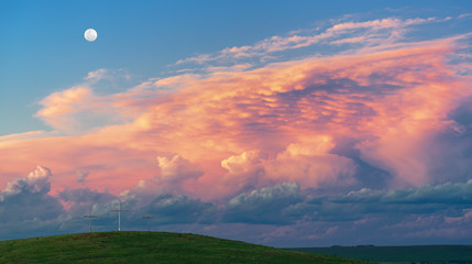Dramatic clouds filling the sky at sunset. Foreground green hill with three crosses