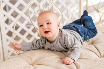 Adorable baby boy in white sunny bedroom. Newborn child relaxing. Family morning at home.