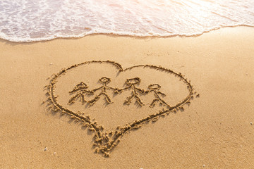 Shape of family holding hands inside heart drawn in sand