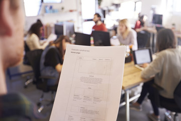 Designer Looking At Website Design Document In Busy Office