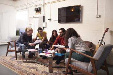Designers Sitting On Sofa Having Creative Meeting In Office