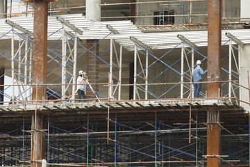 worker making level on steel column