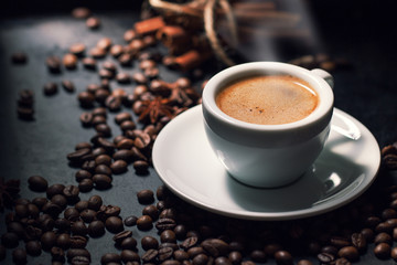 Fresh tasty espresso cup of hot coffee with coffee beans on dark