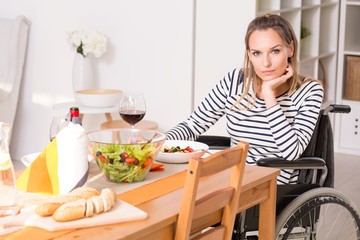 Women on wheelchair sitting at the table.