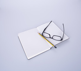 notebook with glasses and pen on the blackground.