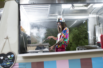 Female in colorful van cooking