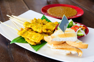 Thai pork satay, grilled pork on white dish with sauce