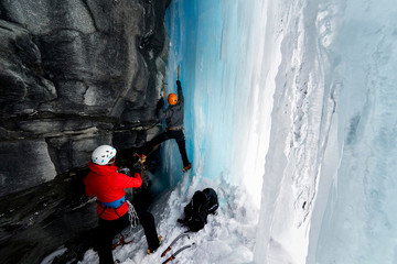 Couple in cave ice climbing, Saas Fee, Switzerland