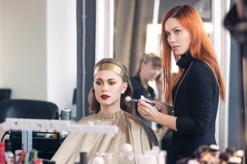 makeup artist makes models eye makeup
