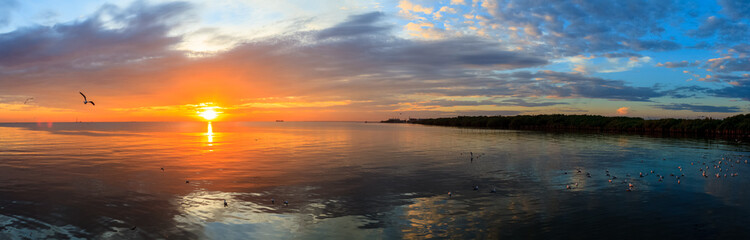 Panorama Tranquil scene cloudy sea sunset with seagulls flying at sunset at Bang Poo Recreational Retreat, Samut Prakan, Thailand.