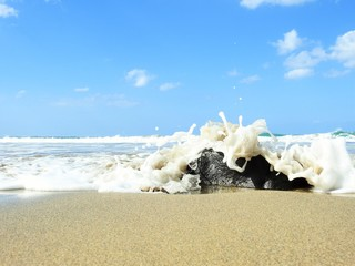 Water hitting a black rock at the beach