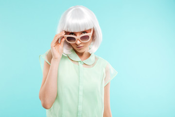 Portrait of beautiful young woman in sunglasses and blonde wig