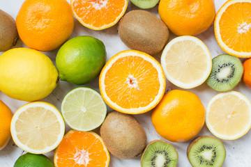 Fruits rich in vitamin C: oranges, lemons, limes, clementines, kiwis, top view, selective focus