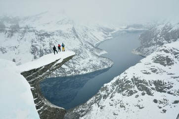 Three boys on famous Troll tongue rock during sever winter in Norway in scandinavia