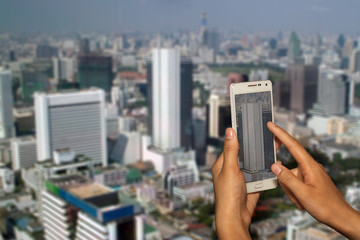 Hand of photographer with smart phone shooting image on blurred Building of Bangkok city background.