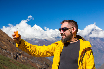 Bearded Hiker taking self portrait with telephone in Mountains