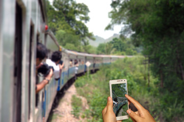 Hand of photographer with smart phone shooting image on blurred tourist on train background.