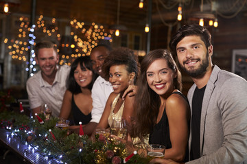 Friends at the bar during a Christmas party look to camera