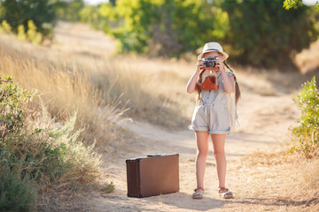 Girl 6 years old with an old brown suitcase and an old camera in hand,brunette with two braids,wearing a straw hat  in a blue flight suit,nature photographs while traveling,standing on a country road