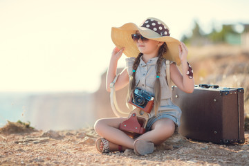 A little girl with pigtails,wearing a straw hat with a large brim,with the old camera around his neck,sitting on top of a cliff,taking pictures of the beautiful nature,the mountains and the sea
