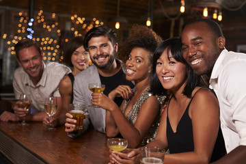 Young adult friends by the bar at a party looking to camera