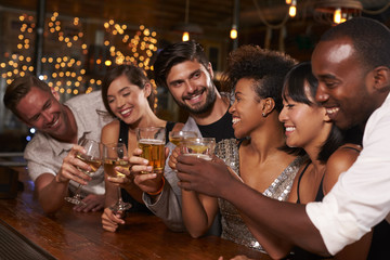 Young adult friends making a toast by the bar at a party