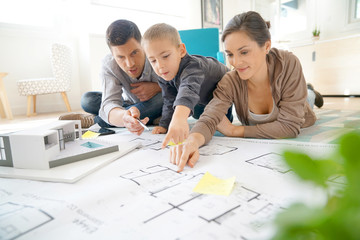 Family at home looking at future house blueprint and model