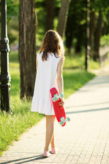 Girl holding a plastic skate board outdoors