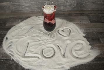 Glas mit Rose und Liebesbekundung im Sand