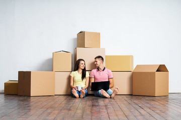 Young couple on the floor next to cardboard boxes