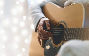 Hipster girl playing guitar in a home atmosphere, person studying on musical instrument on glow bokeh Christmas illimination, hands using guitar in holiday on relax glitter xmas decoration, blur