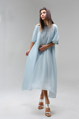 Woman make step in light long blue dress in studio