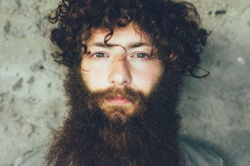 Close up portrait of young male hipster with brown curly hair and beard
