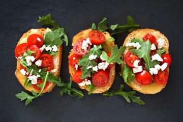 Spoed Fotobehang Voorgerecht Crostini appetizers with cherry tomatoes, arugula, and cheese, above view on slate
