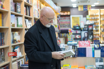 Man is selecting the book from bookshelf in a library.Colored photo