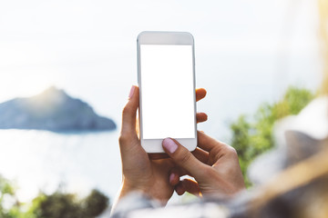Hipster girl texting message on smartphone mobile closeup, hands using gadget phone in travel on background green mountains and sky landscape; finger touch screen cellphone mockup nature, templates