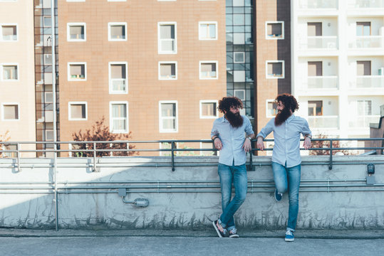 Identical male hipster twins chatting on apartment roof terrace