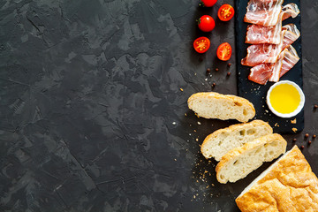 ciabatta, bacon, tomatoes on a black background. top view. idea for breakfast