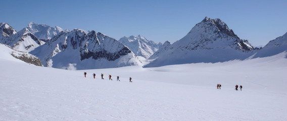 backcountry skiers in the Swiss Alps on a glacier near Disentis