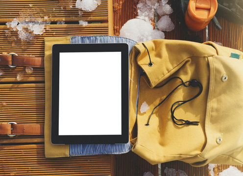 Yellow backpack, thermos with hot drink and hipster gadget tablet with a clean blank screen on a background of winter snow landscape. Technology mockup on wooden pier, templates in travel nature