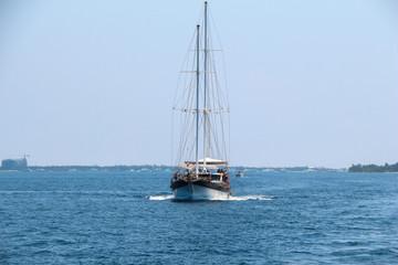 Nautical landscape with retro sailboat. Sea voyage on sailing yacht - luxury lifestyle in summer. Seashore near islands, soft light effect.