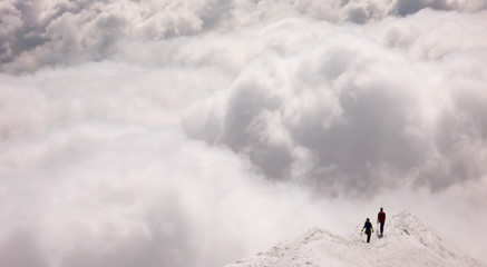 a mountain guide and client on an exposed ridge in the Swiss Alps before an oncoming storm