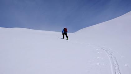 a backcountry skier climbing a mountain in the Swiss Alps near St. Moritz